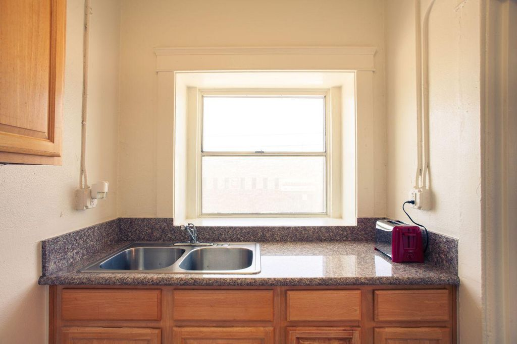 Kitchen area with medium-sized window and sink on the left.