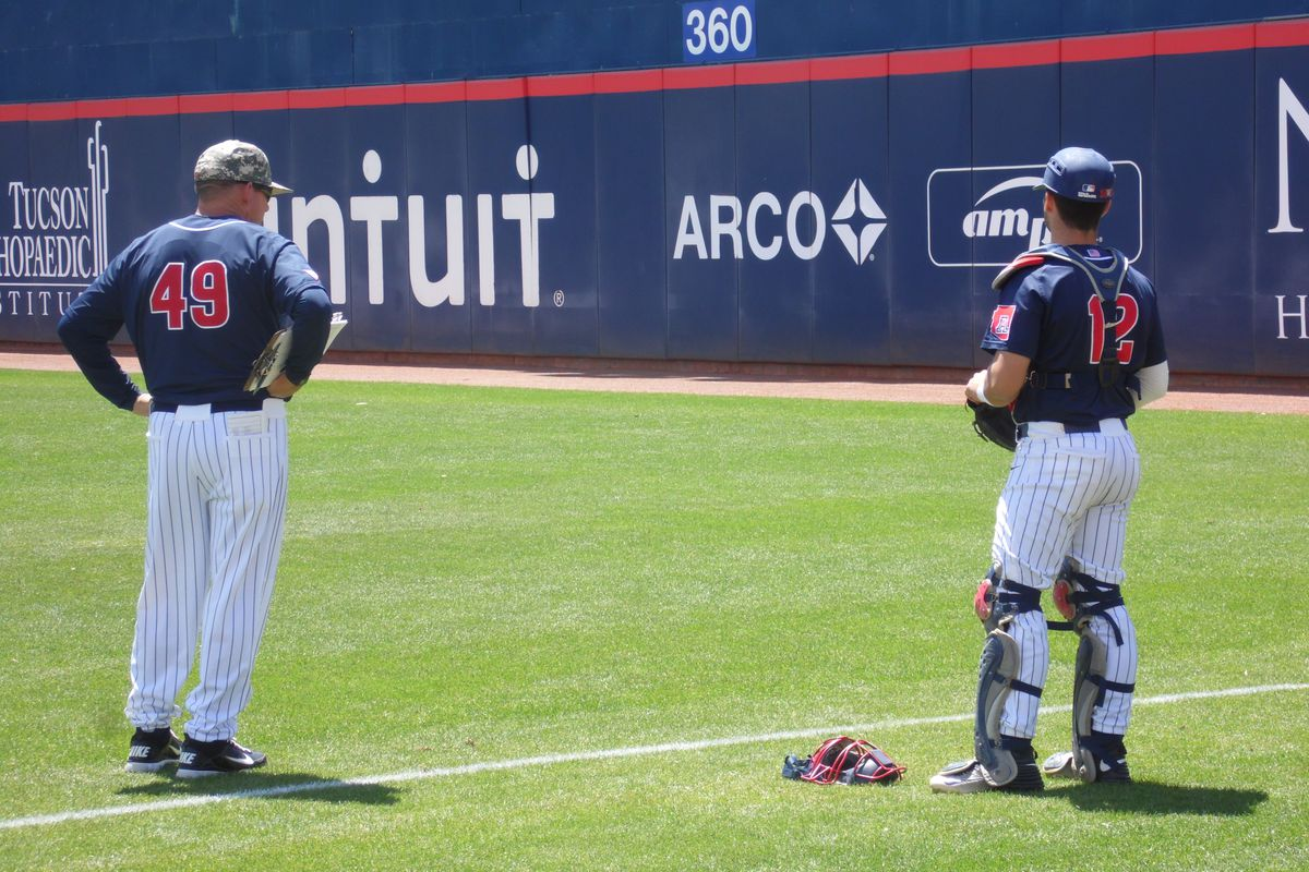 Pitching coach Dave Lawn and catcher Cesar Salazar look on
