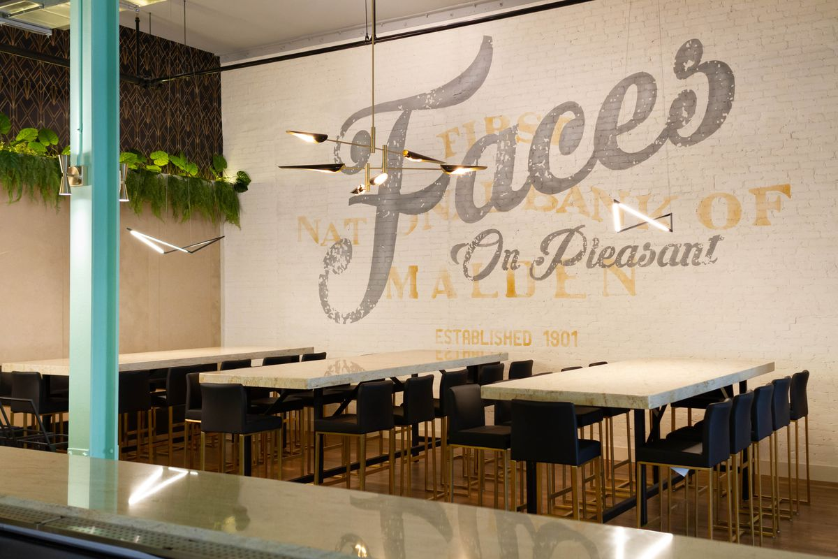 """View of a brewpub dining room through a window frame. """"Faces on Pleasant"""" is painted on the white brick wall, superimposed over an old bank logo."""