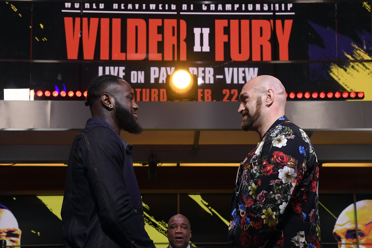 Deontay Wilder and Tyson Fury face off with sportscaster Curt Menefee looking on during a news conference at Fox Studios on January 25, 2020 in Los Angeles, California.