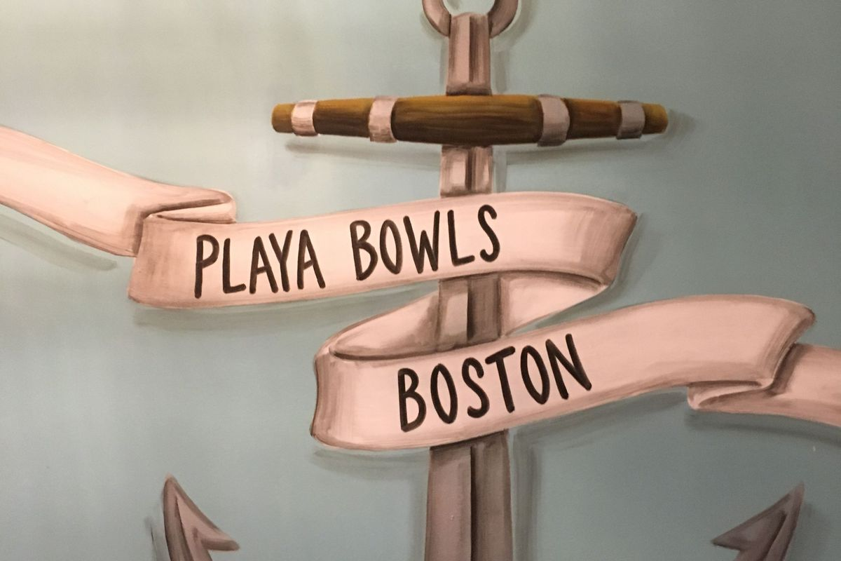 """A silver painted anchor displays a white banner reading """"Playa Bowls Boston"""""""