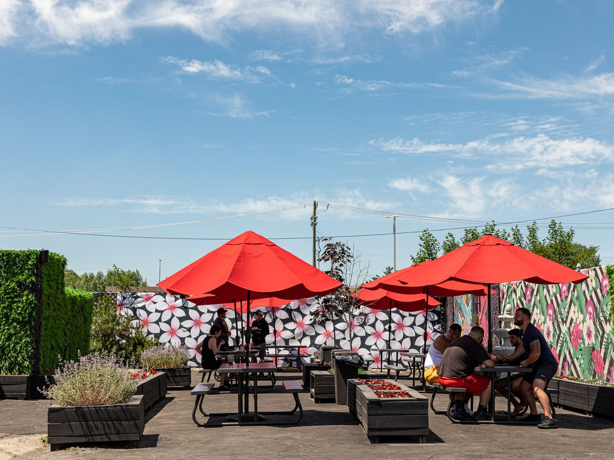 Red umbrellas provide shade to black picnic tables beside the Detroit 75 Kitchen trailer.