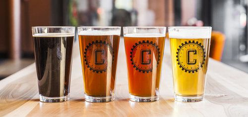 Four pint glasses of beer in ever-darkening shades