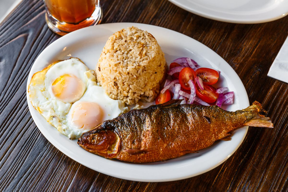 A whole smoked milkfish, two eggs, rice, and a tomato and red onion salad on a white plate