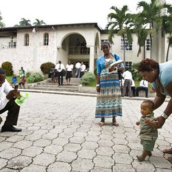 Fabiola Abraham, right, of the Torcelle Ward in Petionville helps her nephew take his first steps where 600 quake survivors lived in January.