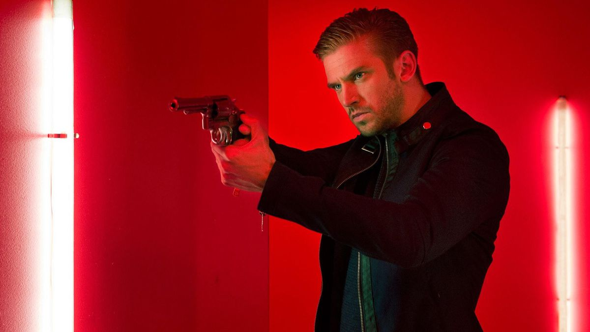 dan stevens holding a gun in the guest