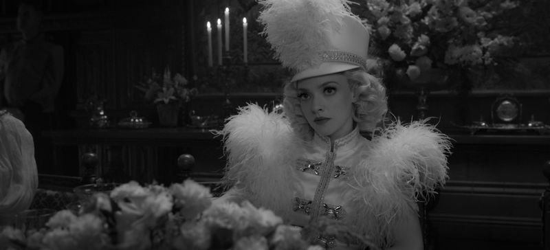 A black and white image of Amanda Seyfried playing Marion Davies, in a circus-inspired costume with a big hat.