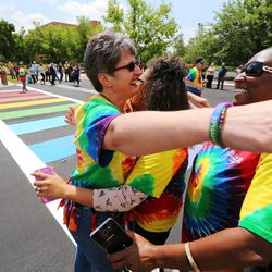 Salt Lake Community College officials and students hug and dance after unveiling a new pride crosswalk at the Taylorsville campus on Monday, June 13, 2016.