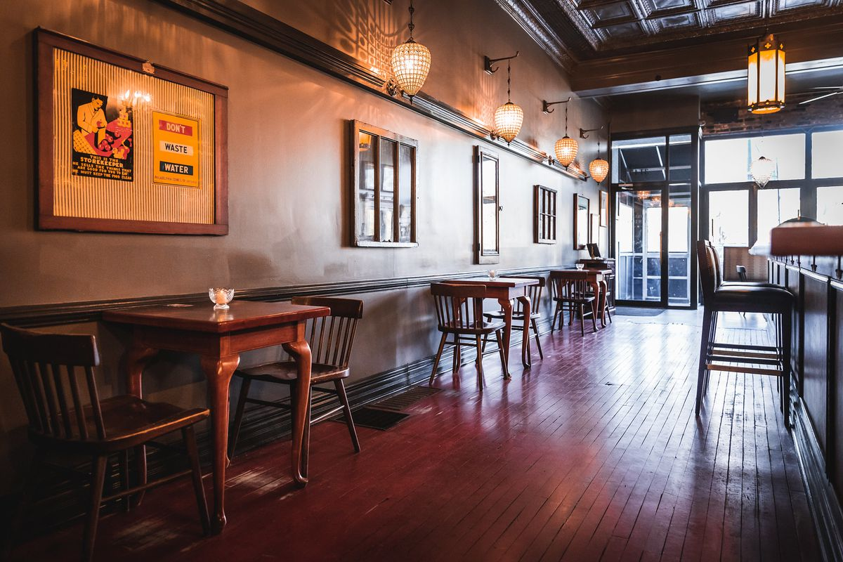 A empty bar with wooden floors and antique art frames.