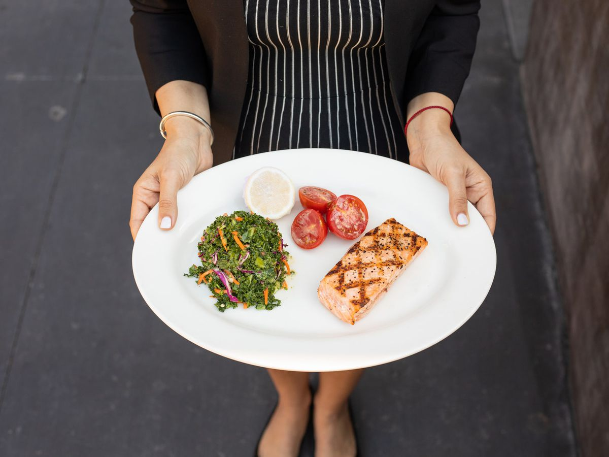 A woman holding a plate of grilled salmon and kale slaw