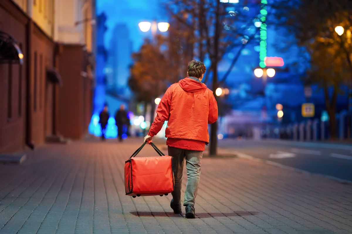 A delivery worker holding a red thermal delivery bag and walking on an empty street.