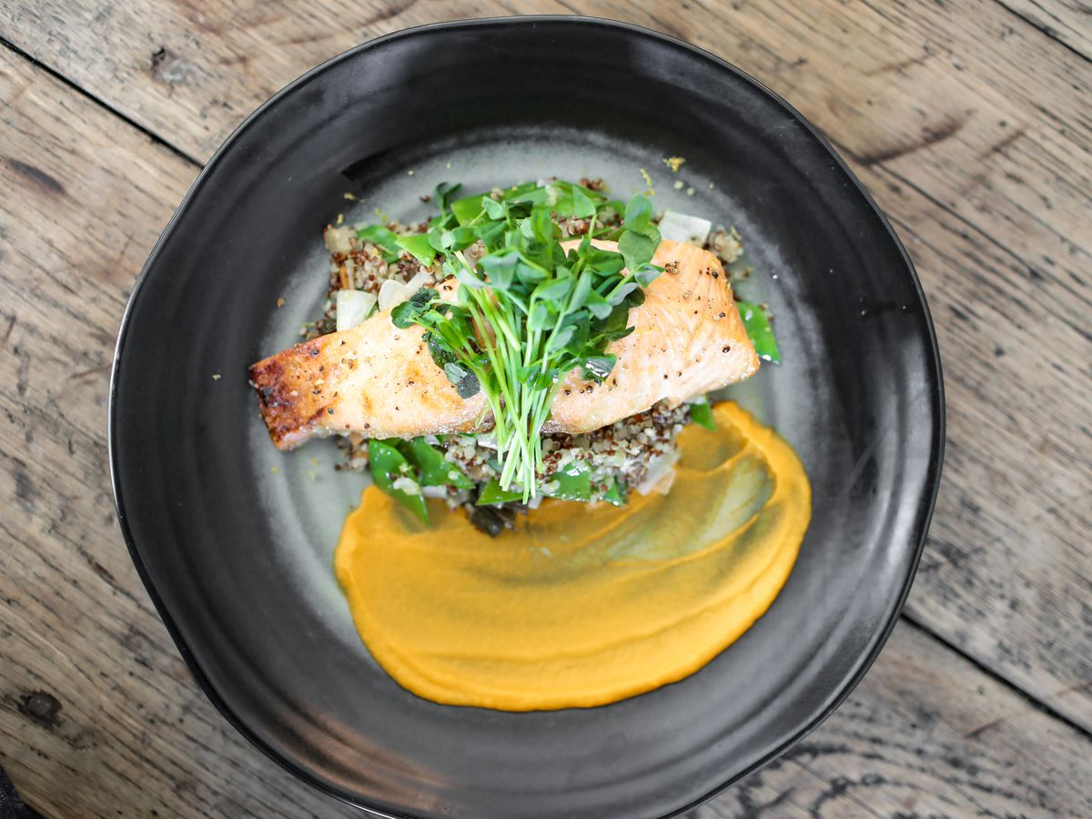Grilled salmon and green herbs with an orange puree on a black plate sitting on a wooden table