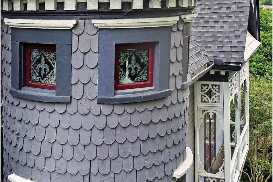 A photo of a victorian home's shingles and small balcony.