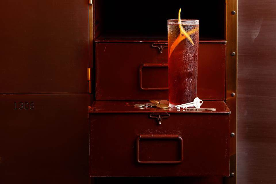 A drink in a highball glass rests on the open door of a safety security box with a key and a few coins lying by its base