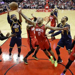 Utah Jazz guard Mike Conley (10) and Houston Rockets forward P.J. Tucker (17) vie for a rebound during the first half of an NBA basketball game, Sunday, Feb. 9, 2020, in Houston.