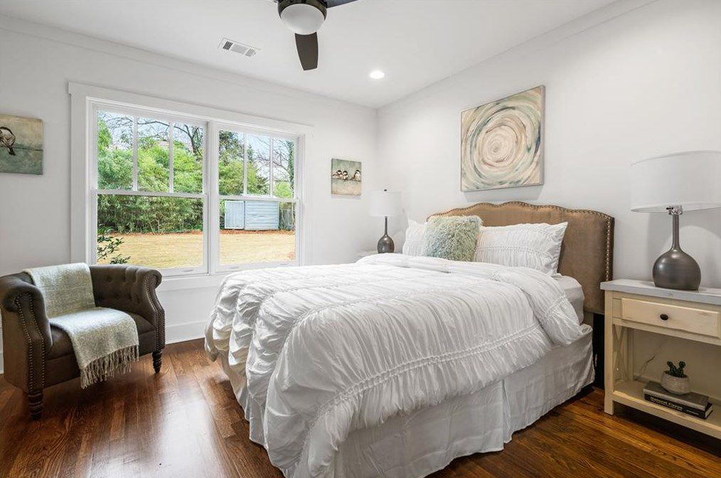 A master bedroom with a huge bed and white walls.
