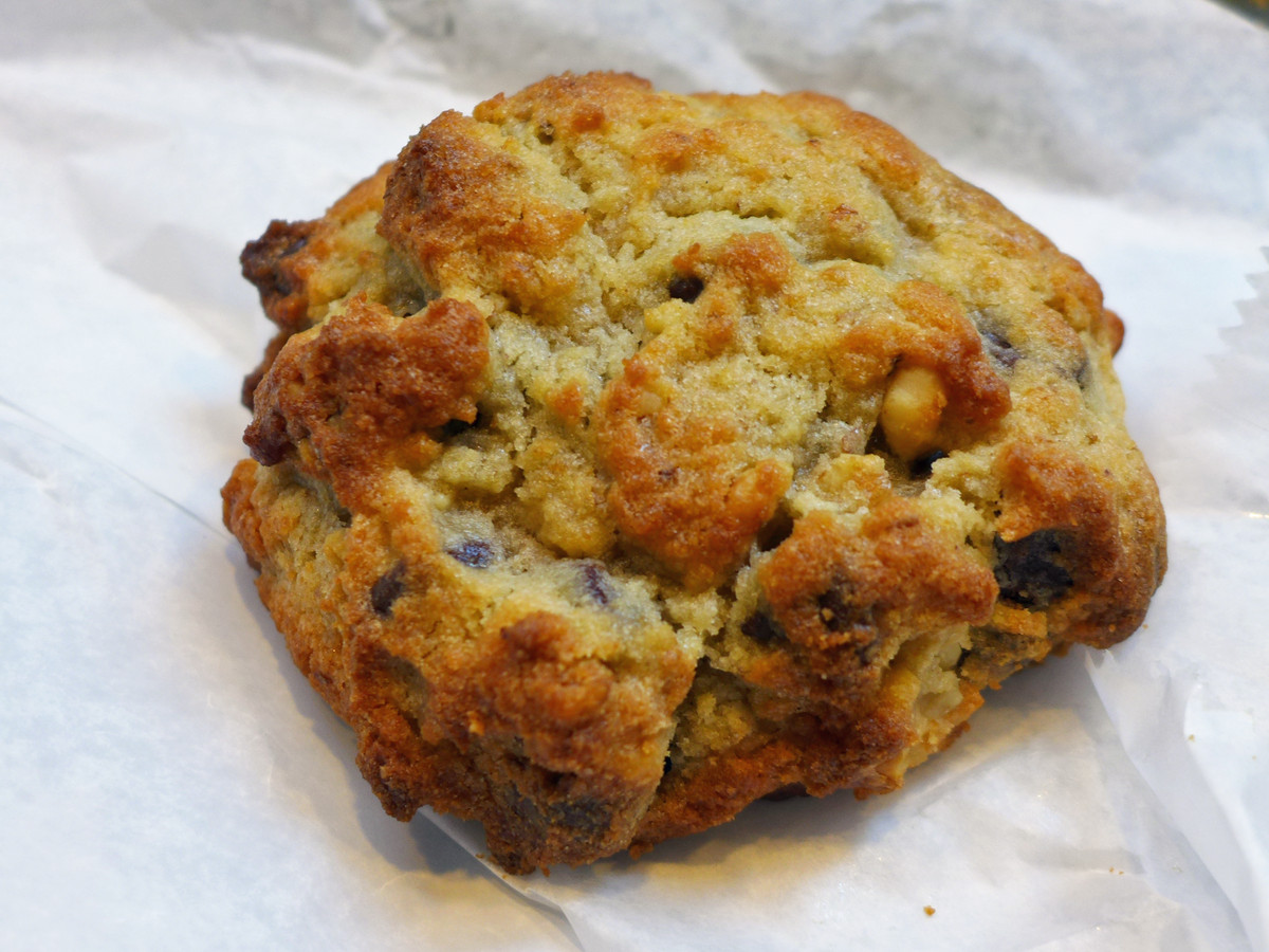 A craggly chocolate chip cookie sits on parchment paper