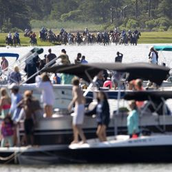 People in boats and on shore watch as volunteers with the Saltwater Cowboys push wild ponies and foals off of Assateague Island, Va., for their swim to Chincoteague Island during the 94-year-old swim tradition of Pony Penning on Wednesday, July 24, 2019. During the event, the horses navigate through the water for a couple hundred yards, and, after resting, are walked down the streets of Chincoteague and eventually end up at a carnival where the foals are actioned.