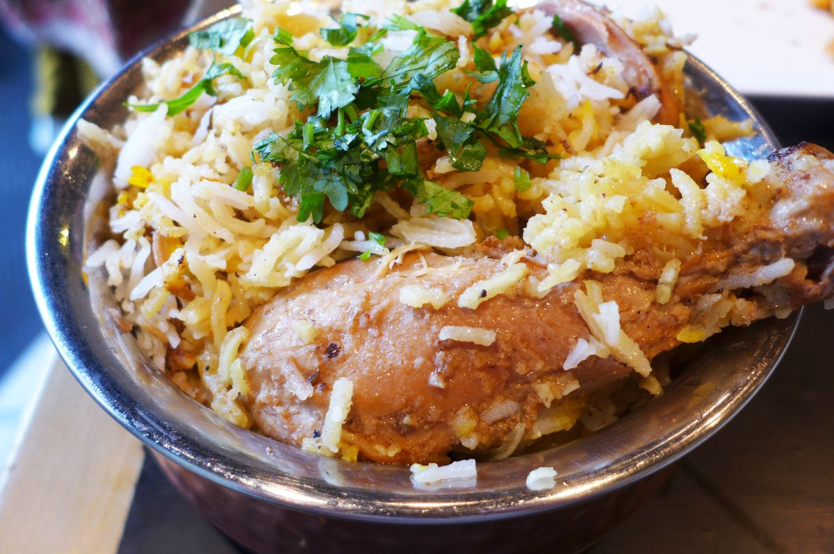 A bowl of chicken biryani with a bone-in drumstick in the foreground.