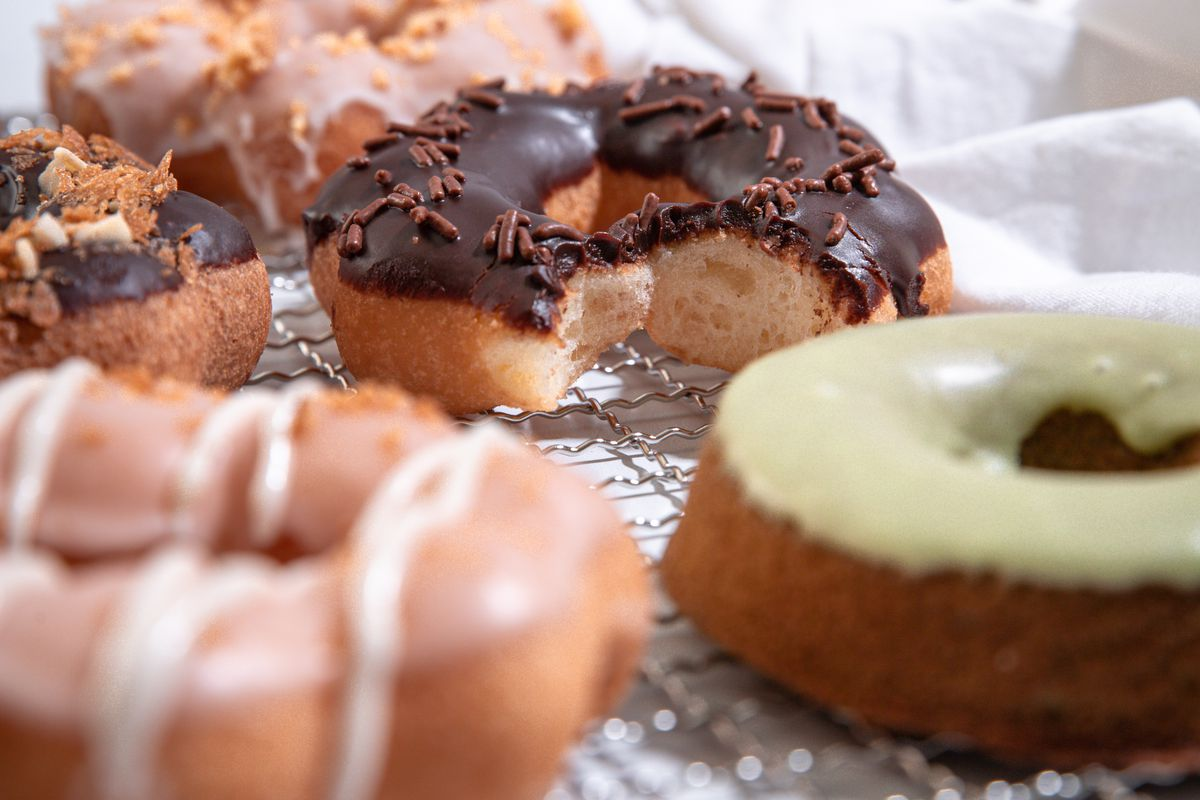Five doughnuts with different colorful glazes sit on a cooling rack at Heyday, a Portland, Oregon doughnut pop-up.