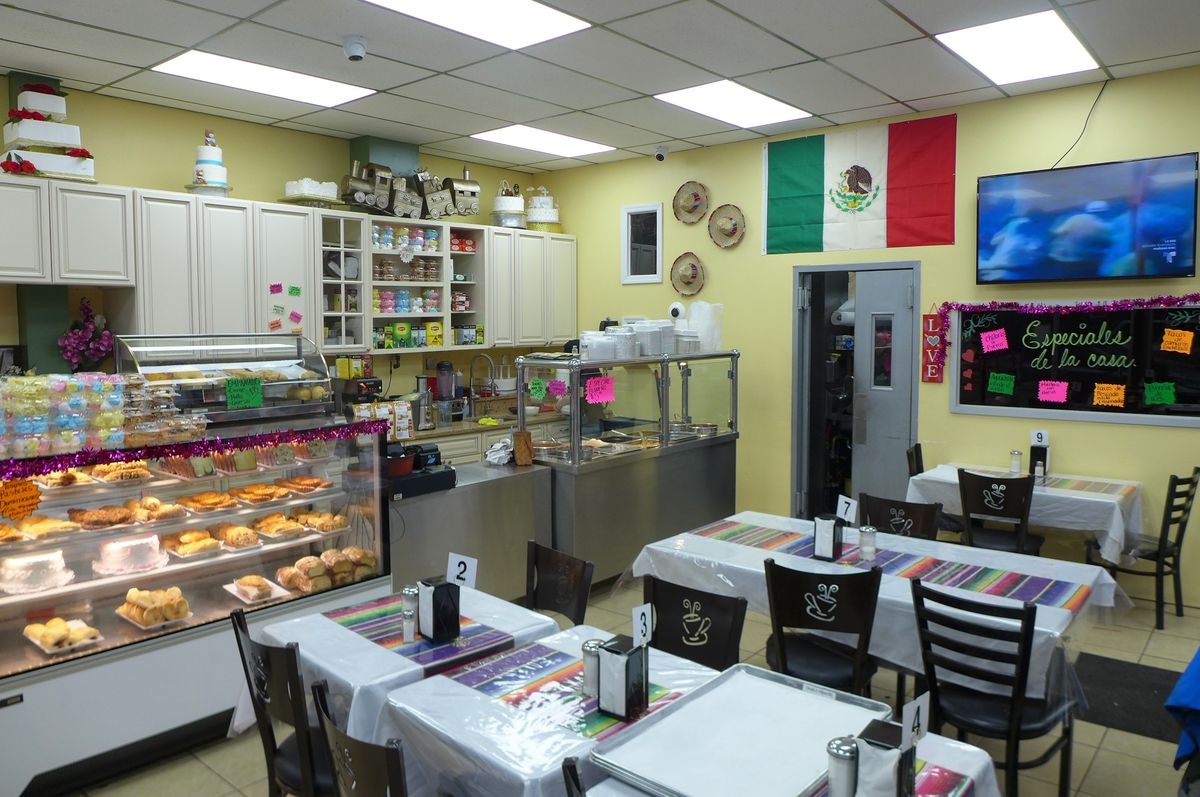 Some tables and pastry display cases in a brightly lit interior.