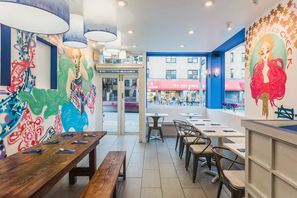 Lamoon's dining room has communal wooden tables and walls with colorful murals.