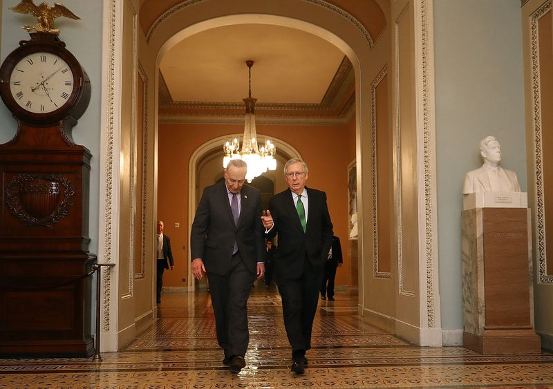 Senate Major Leader Mitch McConnell (R-KY) and Senate Minority Leader Chuck Schumer (D-NY) walk side by side in the halls of US Capitol.