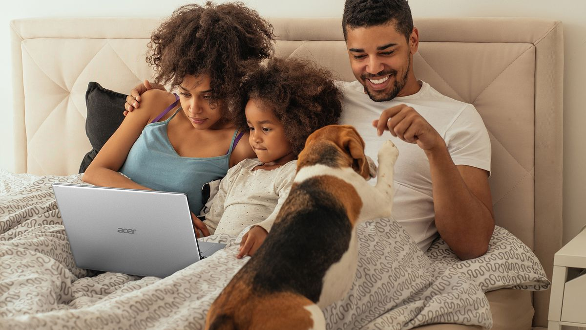 Two parents and a young child watch content on the Acer Aspire 5 in a bed. A dog paws one of the members.