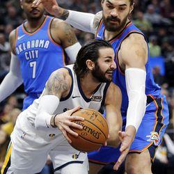 Utah Jazz guard Ricky Rubio is guarded by Oklahoma City Thunder center Steven Adams during NBA basketball in Salt Lake City on Saturday, Dec. 23, 2017.