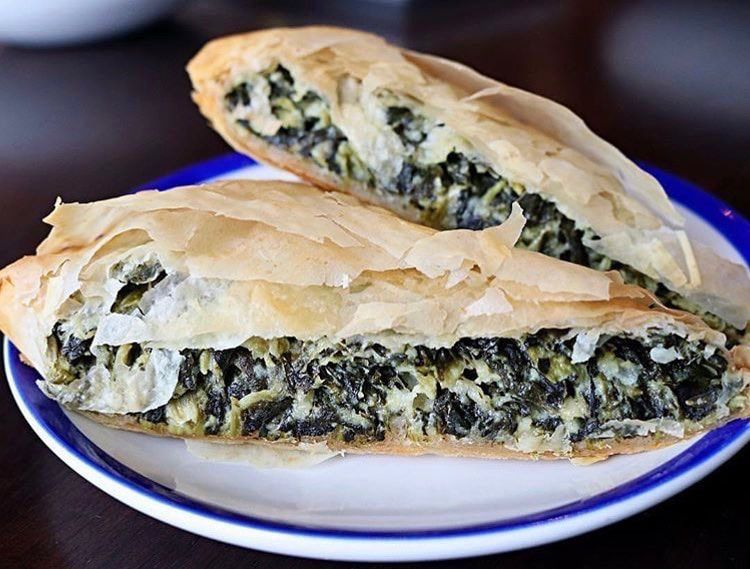 Two pieces of spanakopita sit on a white plate with a blue edge