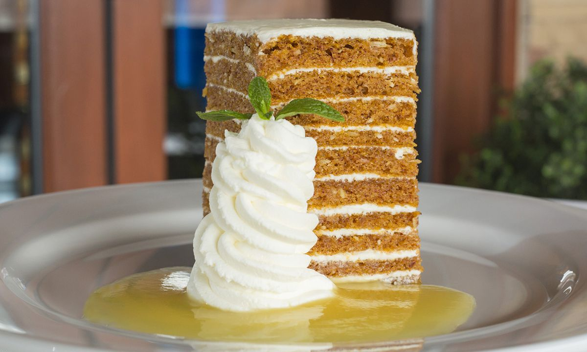 Ocean Prime's tall orange carrot cake features 10 layers and is served with an enormous dollop of whipped cream on a pool of pineapple syrup