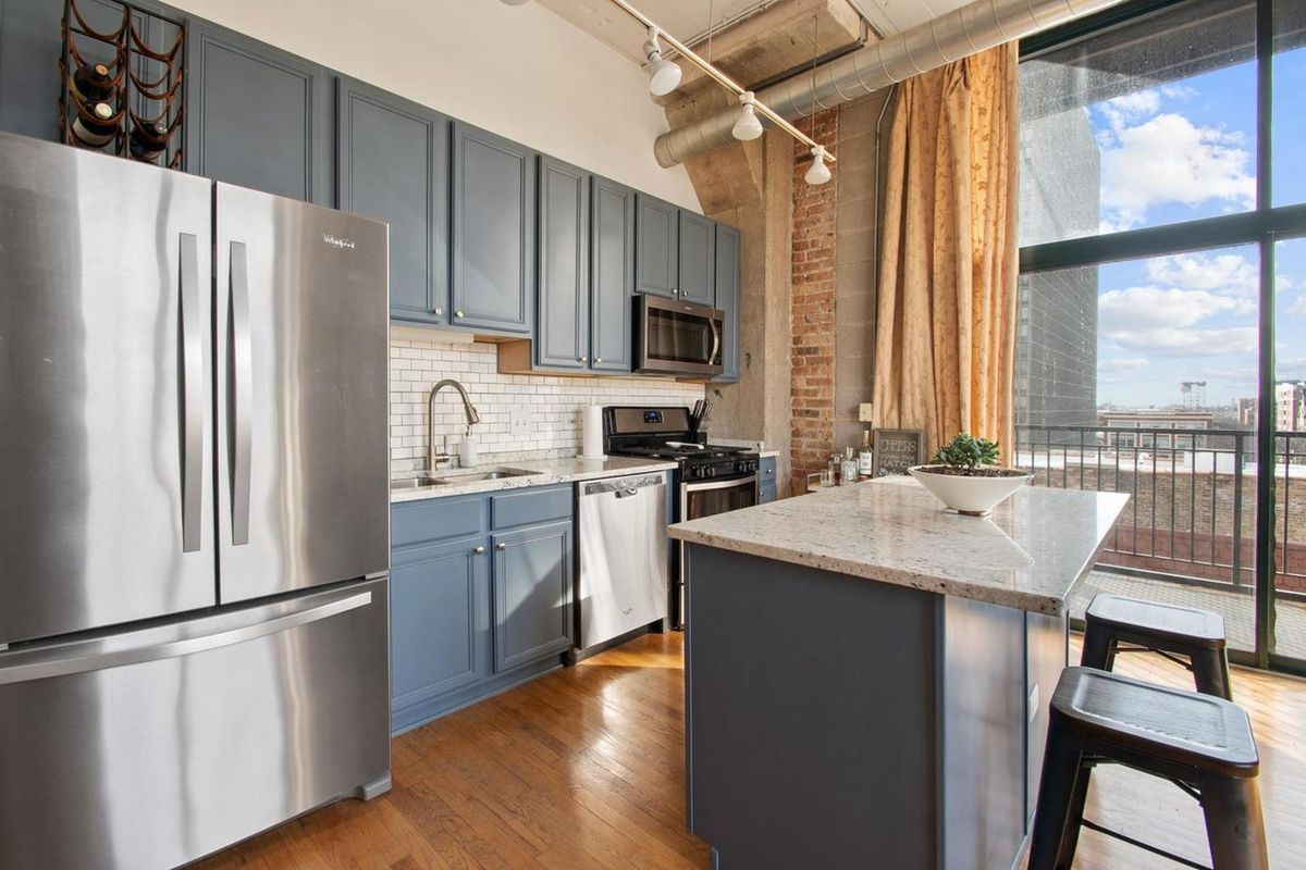 A kitchen with blue cabinets and white subway tile backspash.