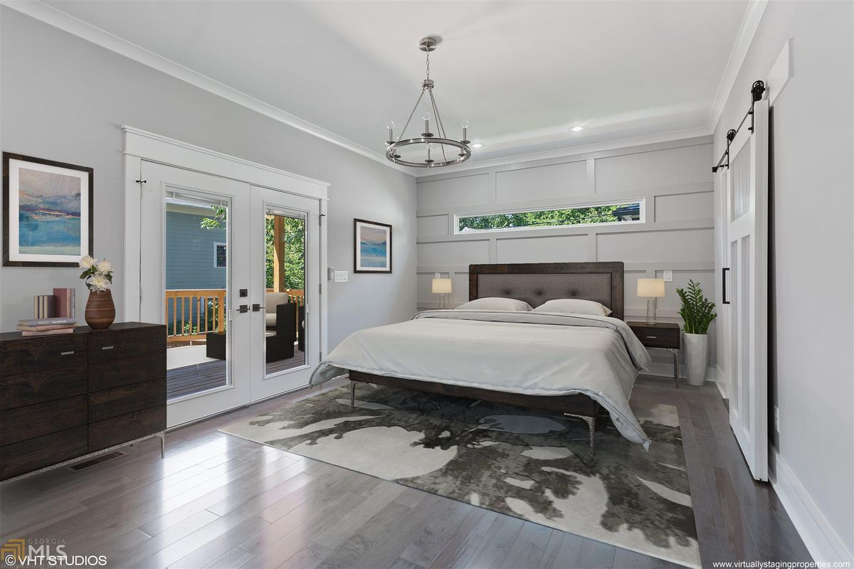 A white and large master bedroom with a sliding door at right.