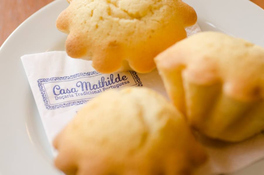 Several small pastries sit on a napkin bearing the CasaMathilde logo on top of a white plate