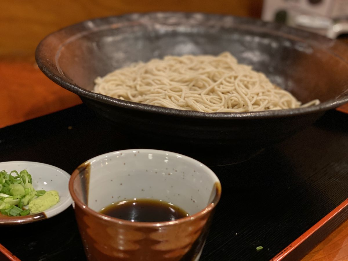A small cup of tsuyu sits in front of cold soba in a bowl