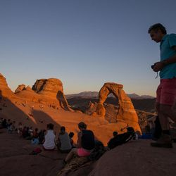 """People gather to watch the sunset at Delicate Arch in Arches National Park near Moab on Thursday, Sept. 8, 2016. More than 5 million people will visit Zion and Arches national parks before the year is over, straining the communities that serve as gateways to the parks.  """"When the population of a community is only 5,000 people and on any given weekend you go to 15,000 to 20,000 people, there are obviously going to be impacts,"""" said Moab Mayor Dave Sakrison."""
