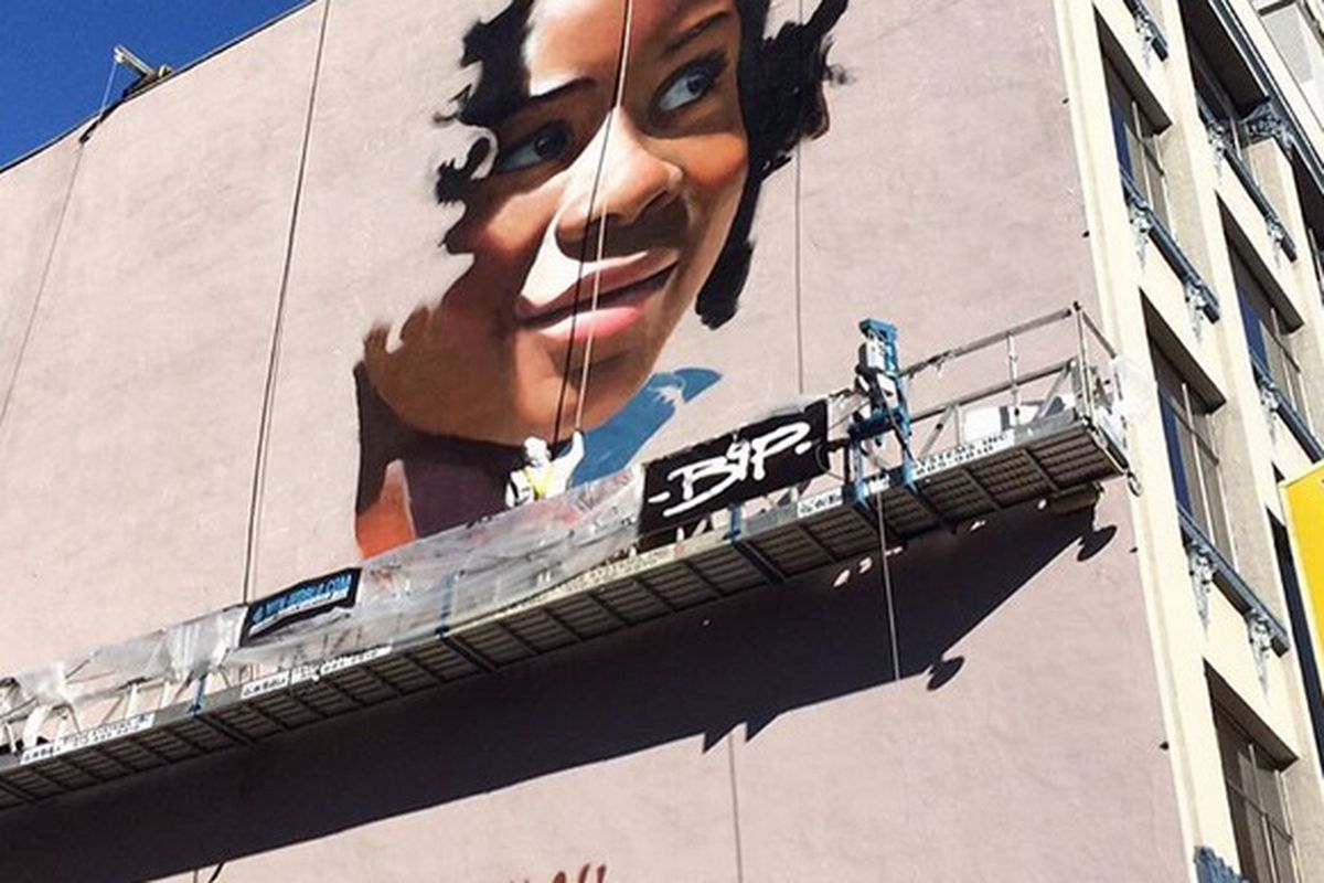 A mural in progress showing a smiling African American woman with a shoulder tattoo on the side of a Mission Street Denny's.