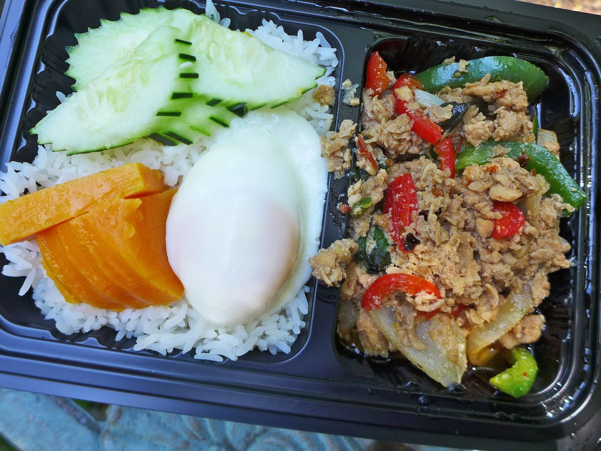 A black plastic carryout tray with a green chicken stir fry on one side, and rice with a poached egg and sweet potato on the other.