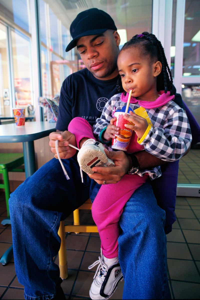 A father ties his daughter's shoes at a McDonald's restaurant.