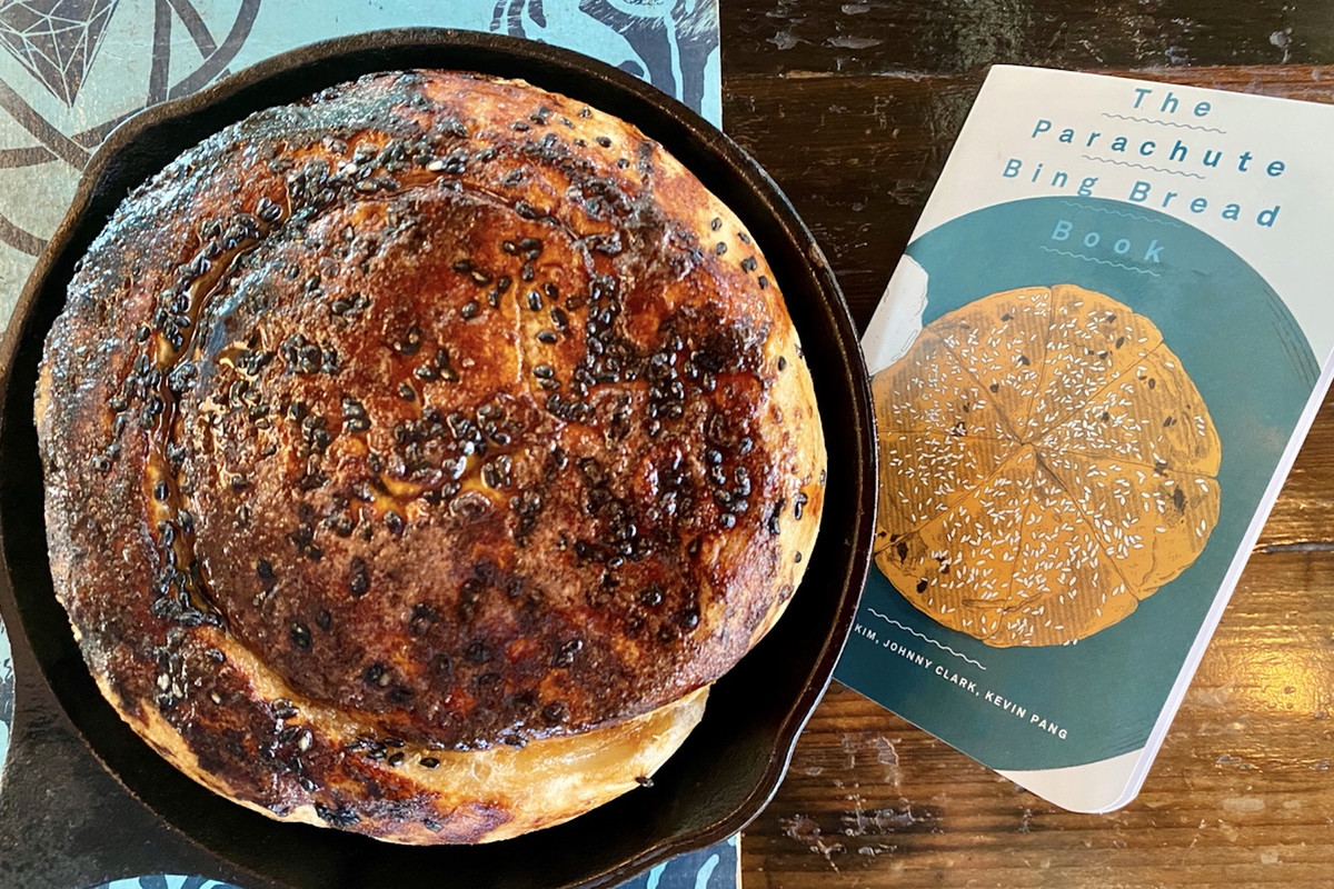 """A cast iron pan filled with Bing bread, next to a book called, """"The Parachute Bing Bread Book"""""""
