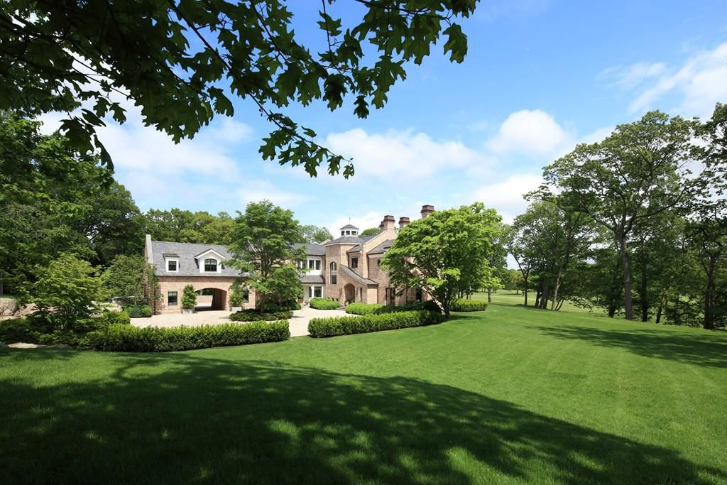 A sweeping, lush lawn in front of a large house.