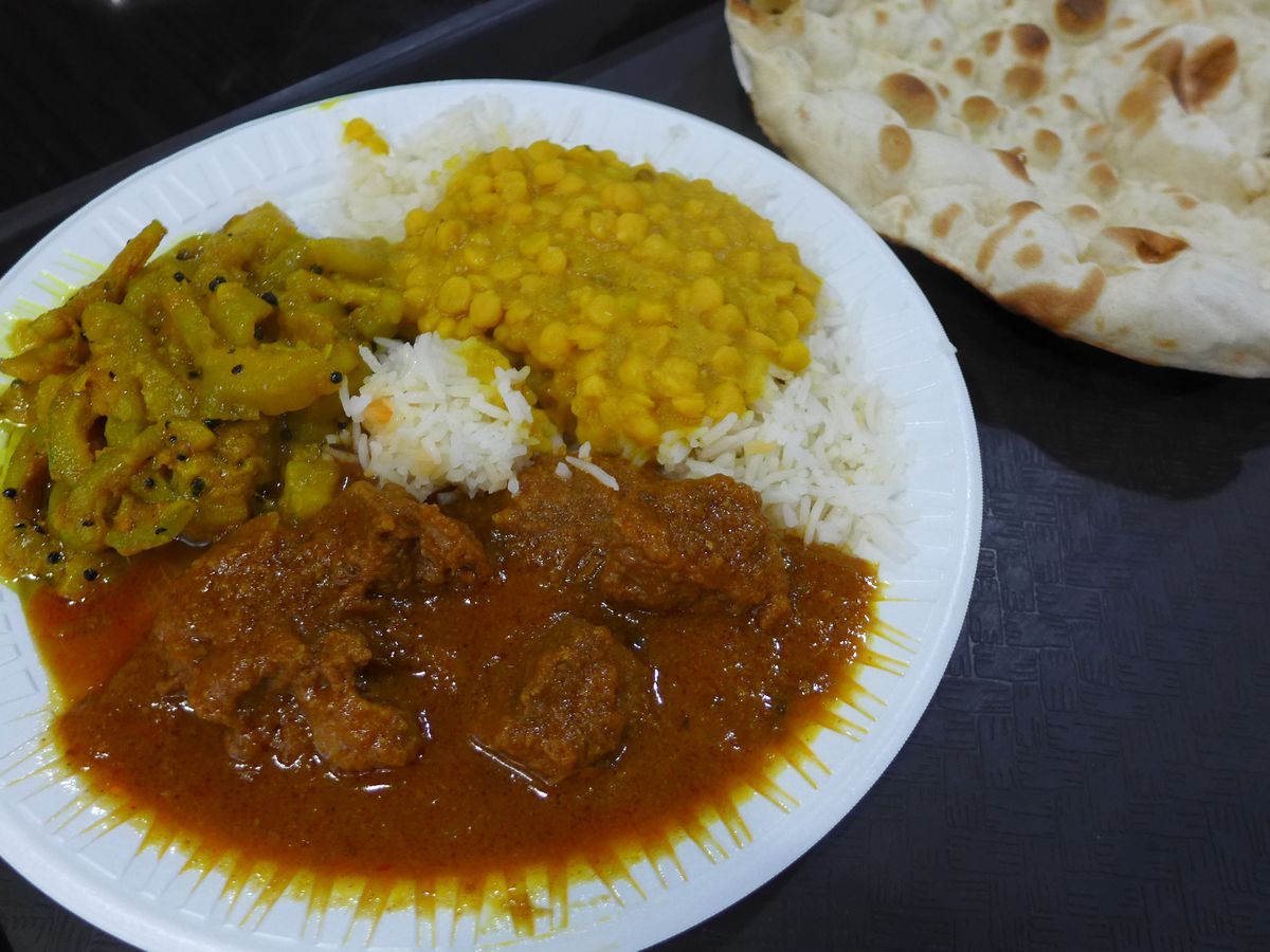 Typical Punjabi steam table stuff, vegetables, meat, and rice on a white plate.