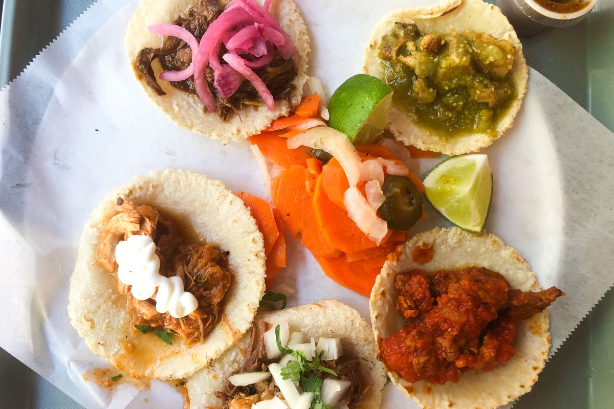 Five miniature tacos sit on a piece of wax paper, with different colored stews with pickled onions, herbs, etc.