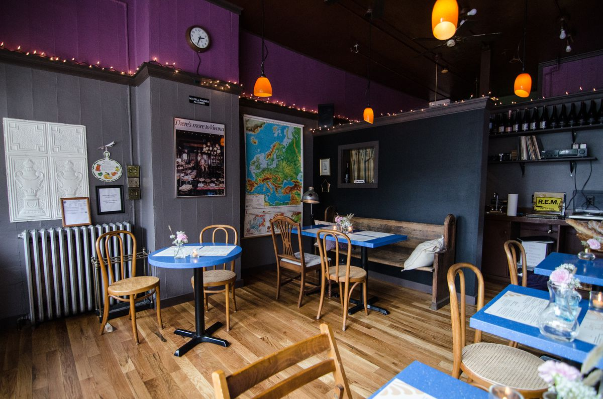 Interior of a dimly lit small restaurant with light wooden floor, gray walls with purple trim near the ceiling, string lights, a large map, and tables with bright blue tops.