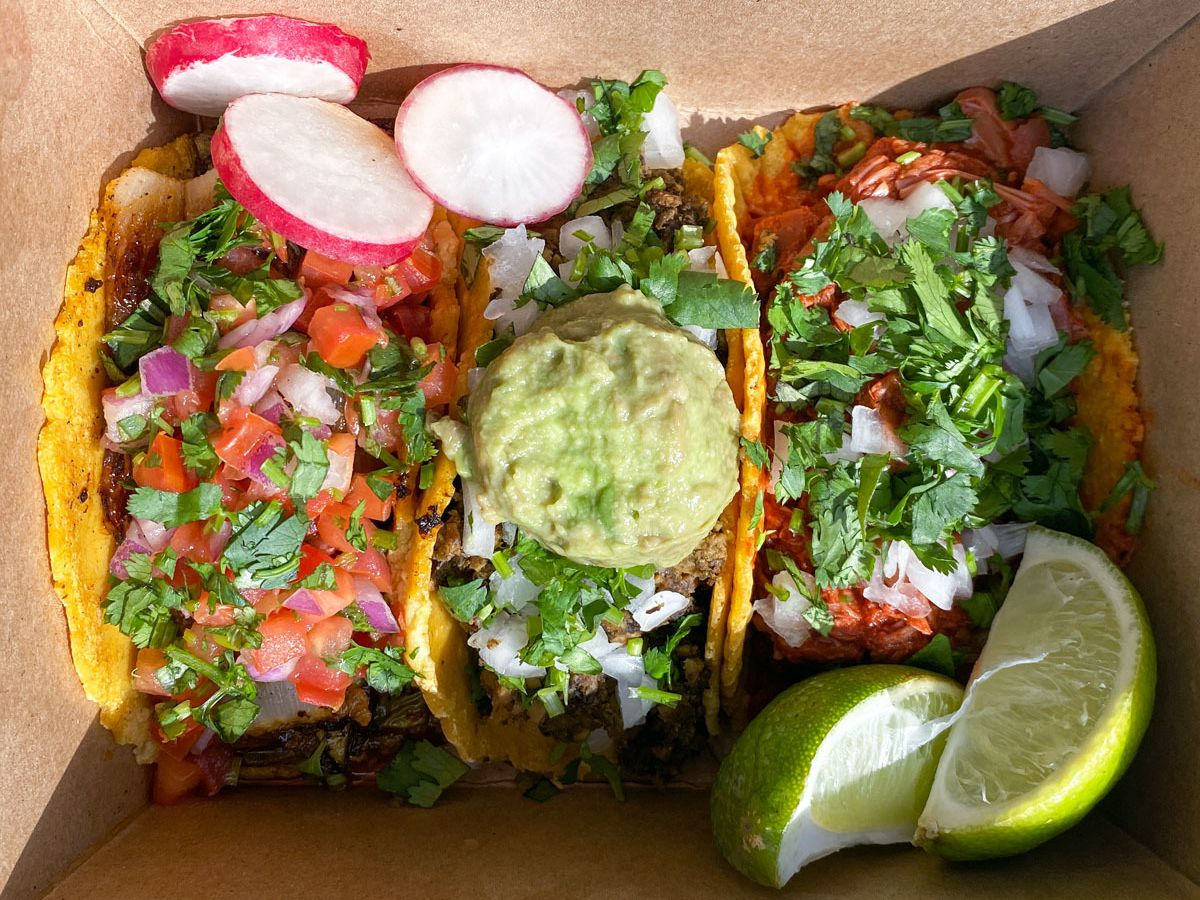 A photo of the nopales, chorizo and potato, and jackfruit birria tacos from La Taquiza Vegana food cart in a takeout box
