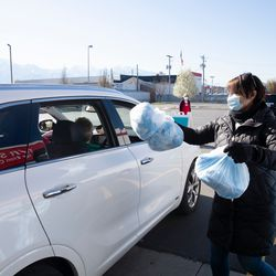 A Project Protect organizer gives clinical face mask kits to a volunteer at a Deseret Industries location in Murray in mid-April 2020. The donation drive-thru areas will be temporarily converted into drive-up locations for volunteers to pull up in their vehicles and pick up the kits. Additional participating Deseret Industries locations include American Fork, Harrisville, Layton, Murray and Riverton.