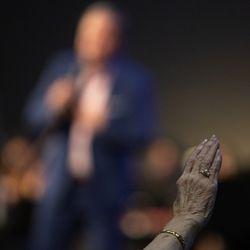 A parishioner raises her hand during a church service at Kingsland Baptist Church in Katy, Texas, on Sunday, March 28, 2021.