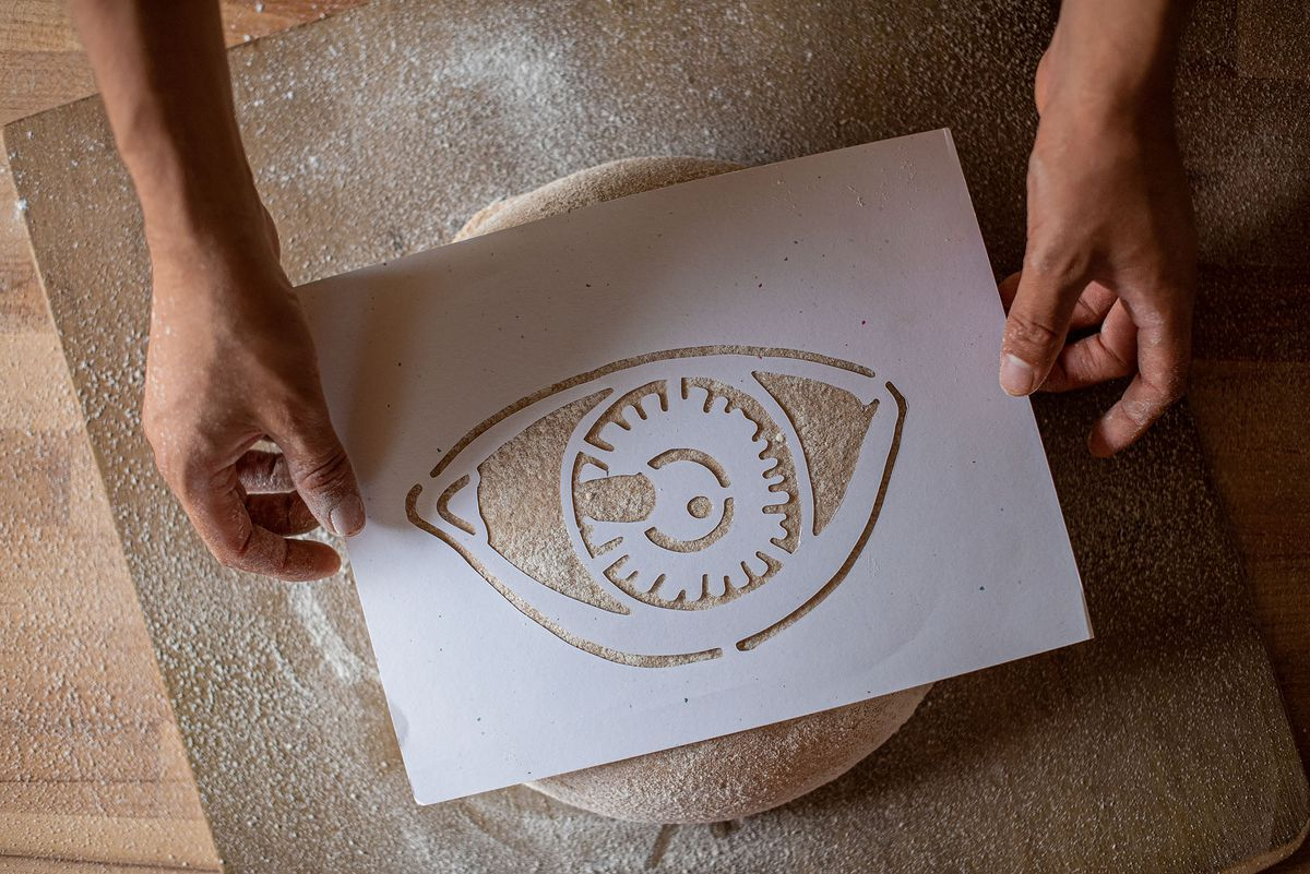 A baker adds a logo to the top of raw dough.