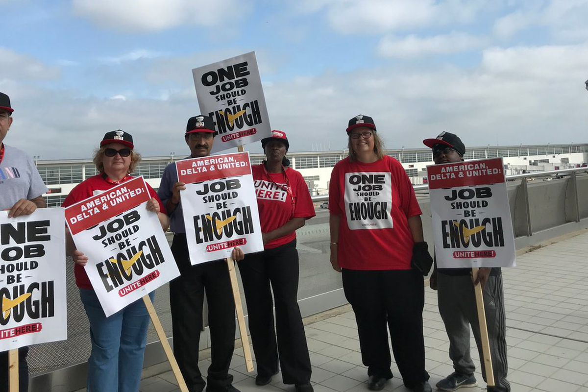 A group of airline workers picketing with signs that read 'one job should be enough'