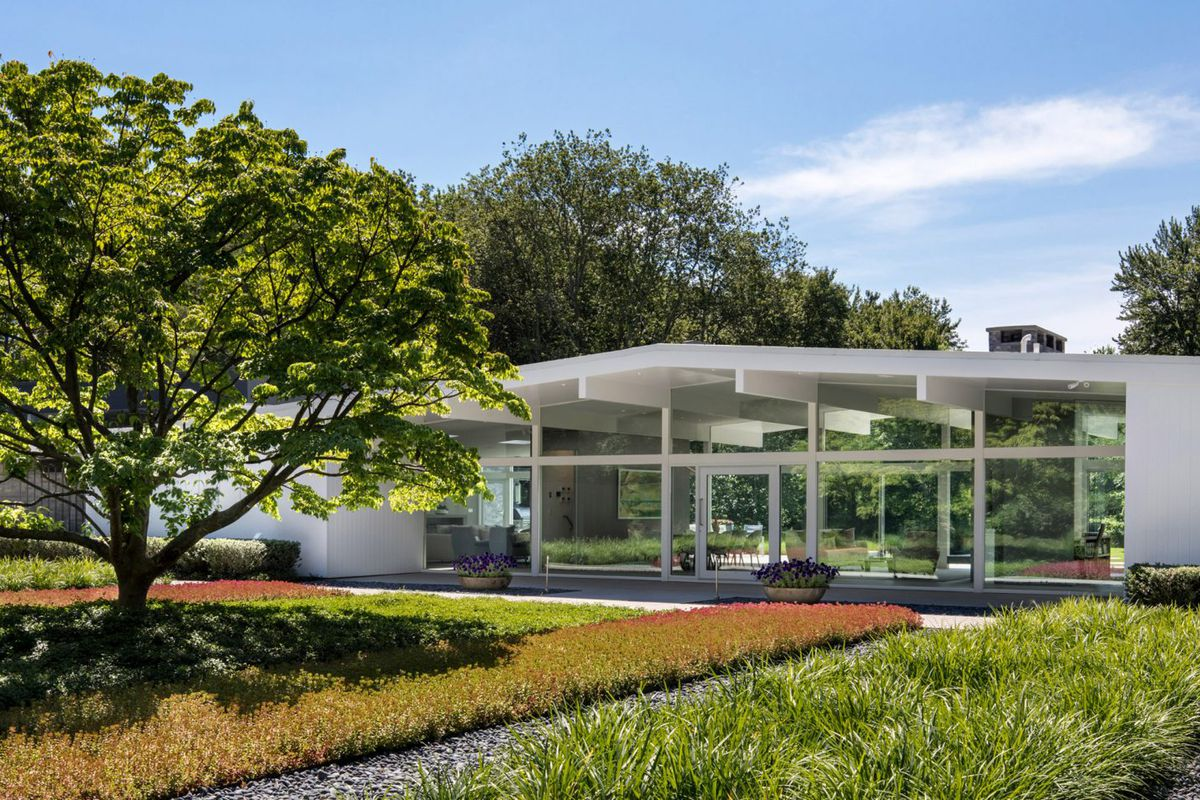 Low-slung home with broadly sloping pitch roof with walls of glass and landscaped grounds.